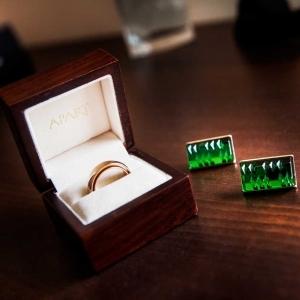 obrączki ślubne i zielone spinki
